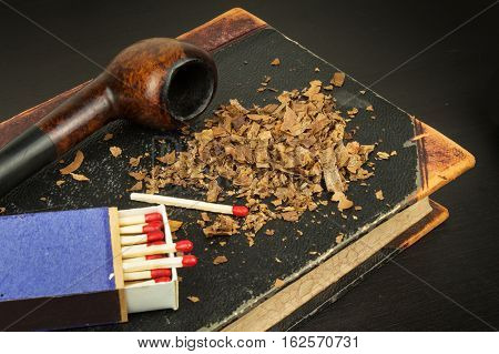 Smoking pipe and antique books. Tobacco pipe on ancient books. Relax by reading old books. Smoking. Risk of cancer.