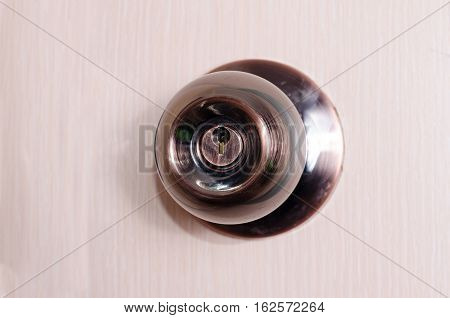 round door handle with a latch on a background of pink door