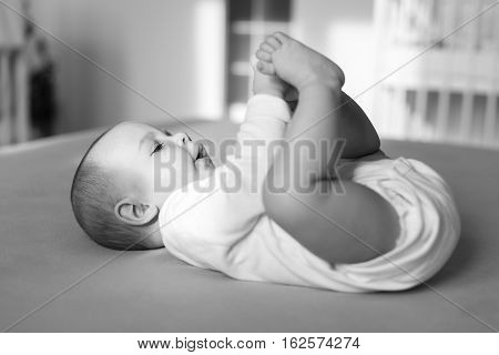 happy baby playing with his feet black and white