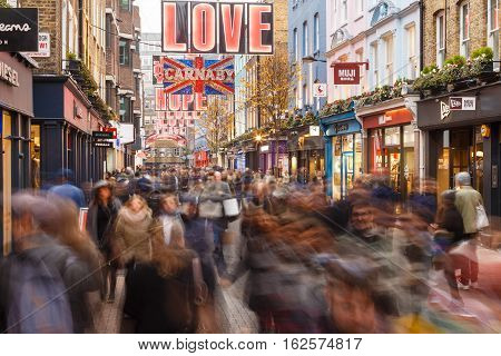 LONDON ENGLAND - DECEMBER 17: Lots of people Christmas shopping on Carnaby Street London. In London England. On 17th December 2016.