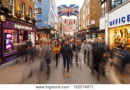 LONDON ENGLAND - DECEMBER 17: A blurred 'sea' of Christmas Shoppers on Carnaby Street London. In London England. On 17th December 2016.