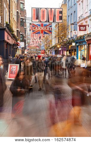 LONDON ENGLAND - DECEMBER 17: Lots of Christmas shoppers on Carnaby Street London. In London England. On 17th December 2016.