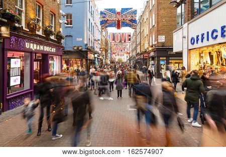 LONDON ENGLAND - DECEMBER 17: Motion blur of Christmas shoppers on Carnaby Street London. In London England. On 17th December 2016.