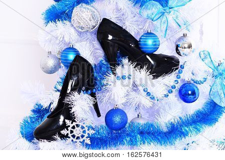 white fluffy christmas tree decorated with colorful blue balls with silver snowflakes new year decorative beads and garlands or festoon with black patent leather shoes on white studio background