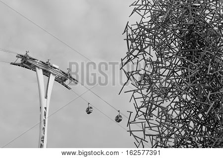 Gondola lift in old stylish photo. Silhouette of air-cable car over gray background.
