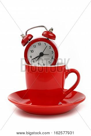Red Alarm Clock In Coffee Cup Over White