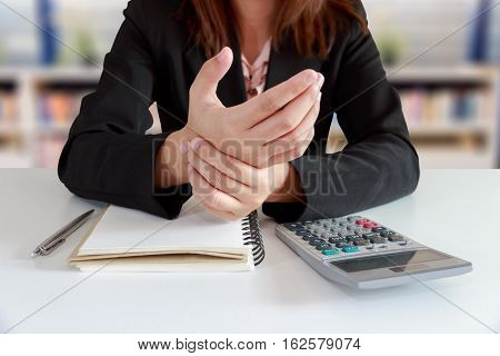 Businesswoman hands pain on desk office syndrome concept with notebook and calculator