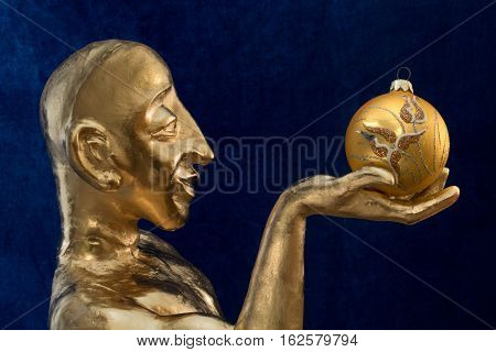Gilded statuette with a ball on the blue background