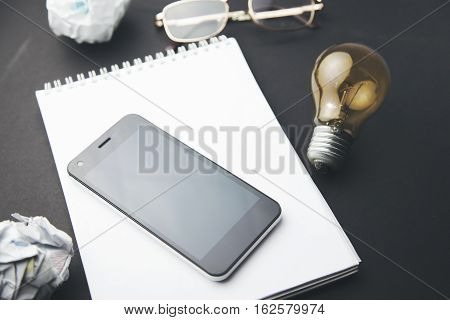 black smart phone with notebookglassespapersand bulb with copy space