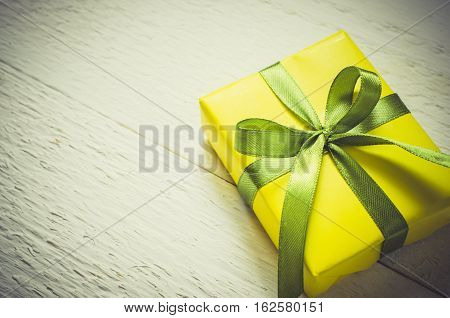 Present for Mother's day Valentine's or birthday. Gift box wrapped in yellow paper with a green ribbon on white wooden background. Vintage Style. Toned Image. Copy space. Selective focus.