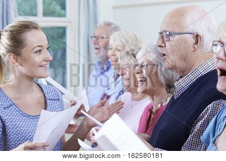 Group Of Seniors With Teacher Singing In Choir Together