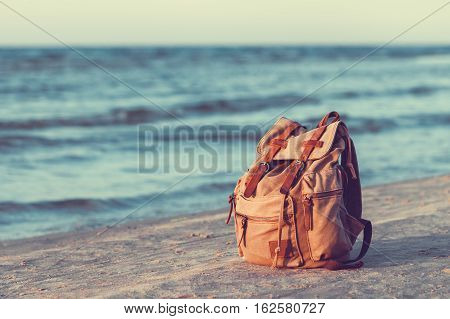 Travel Canvas Backpack on Sea Beach. Retro styled.