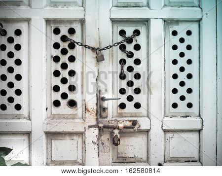 Padlock and iron chain on an old white door