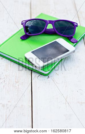 Notebook mobile phone and sunglasses on a wooden table