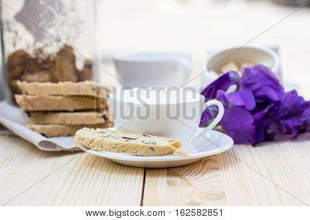 Biscotti and coffee with dried cranberries on wooden background