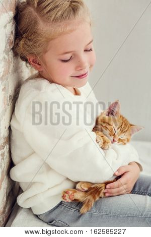 cute little girl holding a kitten on a ginger hand on a white background