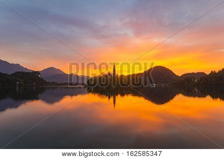 Amazing View On Bled Lake on Sunset. Autumn in Slovenia, Europe. View on Island with Catholic Church in Bled Lake with Castle and Mountains in Background