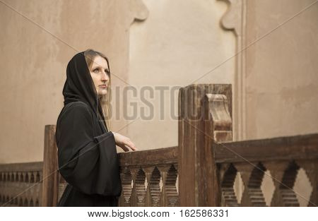 young woman in a traditional emirati dress called abaya in an old castle in Oman