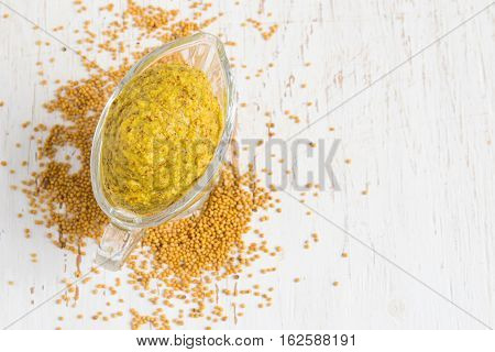 French mustard sauce and mustard seeds on white background. Top view with copy space