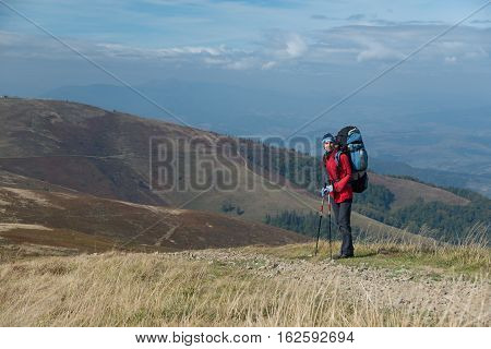 Tourist dressed in bright red windbreaker with sticks and big backpack in mountains.