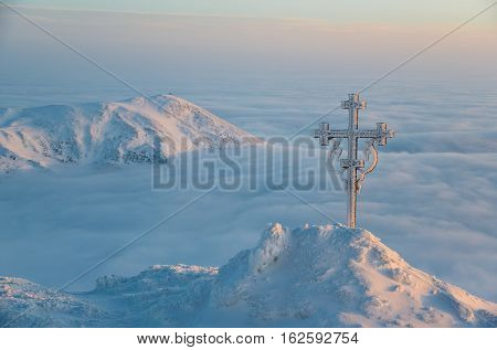 Beautiful winter landscape - sunrise scene in mountains. Christianity cross decorated with frost. Such nature scene cheerful and optimistic. Such faith symbol emphasizes belief.