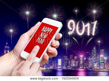 Hand holding mobile and send happy new year message with night cityscape building and 2017 firework at backgroundModern lifestyle celebration.