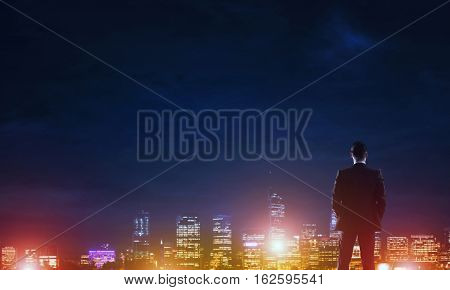 Elegant businessman in suit looking at night city