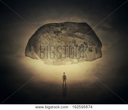 Surrealistic image as a man with a bag in his back stand in a foggy street below a huge squeezing rock. Life pressure and stress concept.