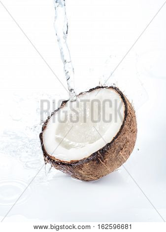 Cracked coconut with water splash isolated on white background