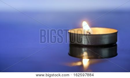Light scented candle, circular, over blue background.