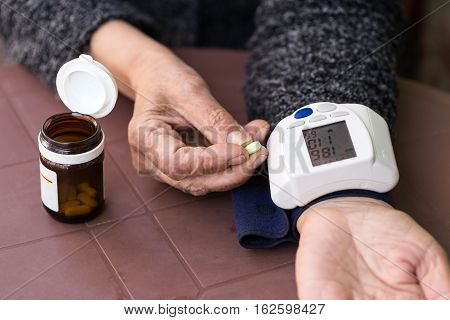 senior woman measuring blood pressure at home, hypertensive