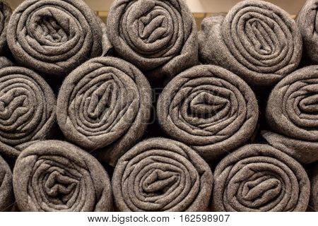 Rolls of many grey plaids stand on the shelf