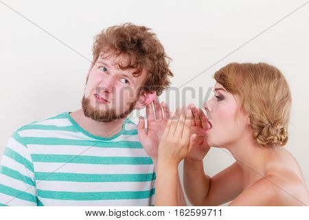 Closeup woman telling an astonished surprised man some secrets couple talking