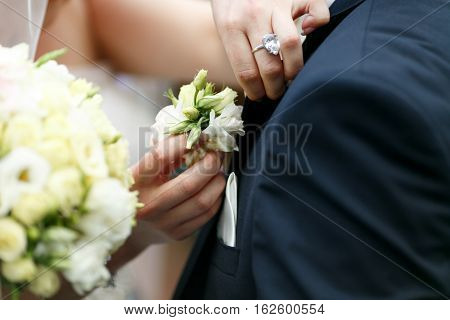 Delicate bride's hands pin a boutonniere in groom's jacket
