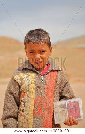 PETRA, JORDAN, MARCH 12, 2016: Portrait of a  little bedouin boy who sells postcards