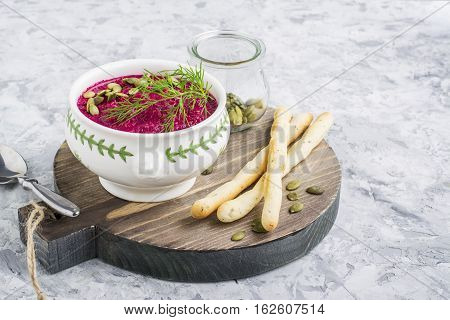 Spring light fresh beet cream soup in portion bowl on a wooden board for feeding with bread sticks. Top
