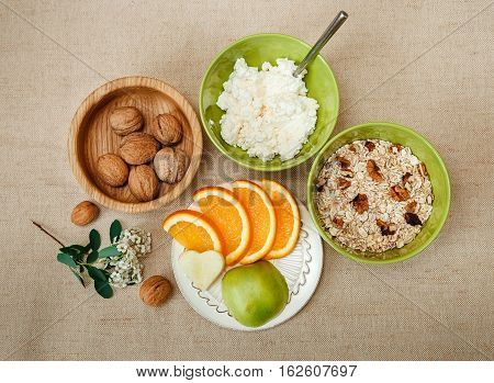 able Appointments for Healthy Organic Breakfast.Walnuts,Oatmeal and Cottage Cheese.Cut Orange and Apple.Green Ceramic and Wooden Plates with Flowers.