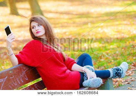 Nature outdoor technology social concept. Gorgeous girl taking selfie. Young lady in park takes picture of herself amidst autumnal vegetation.