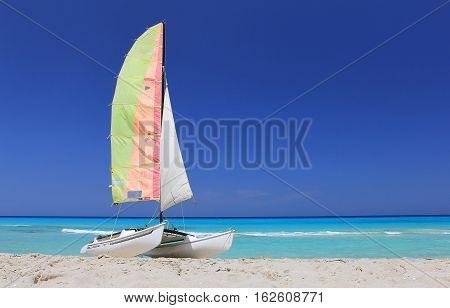 blue sky turquoise Caribbean Sea Atlantic ocean wave relax summer vacation Cuba Cuban beach beachfront white sand sail sheet yacht pleasure boat catamaran