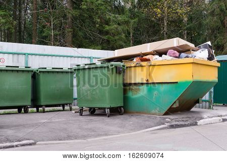 Garbage container with household waste on special area on forest background