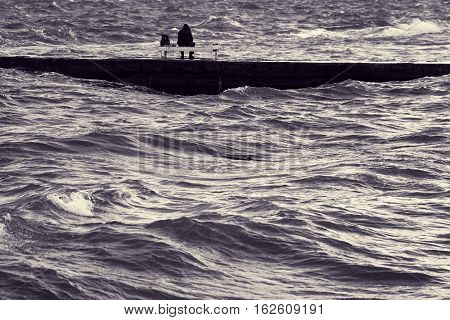 Lone fisherman on pier. Man sitting on deck chair in middle of stormy sea. Beautiful surging waves on water. Fishing in turbulent weather. Loneliness and solitude. Toned black and white color processing. Nice soft warm light