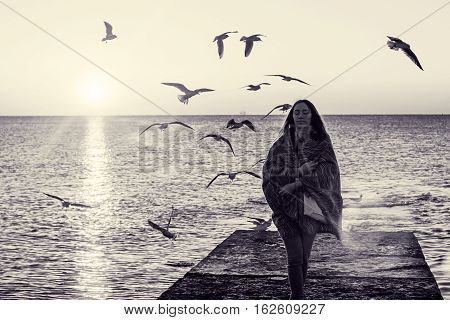 Emotional portrait of girl on pier. Beautiful brunette in plaid meets dawn at sea. Autumn seascape. Flock of seagulls flying in air on sunny morning. Peace and tranquility. Toned black and white color processing. Nice soft warm light