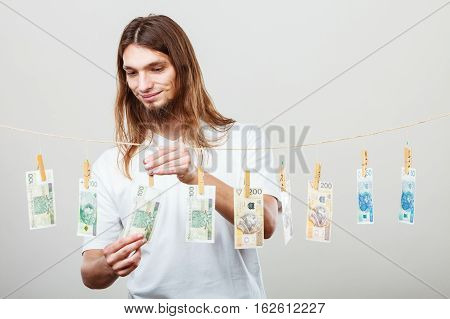 Riches and fortune. Young happy man with a lot of money on grey background. Winning the lottery concept.