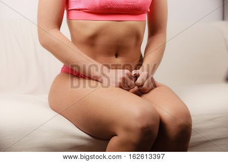 Woman Fit Slim Tanned Body Sitting On Couch