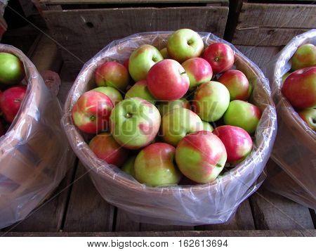 A bushel basket of apples on a farm stand display shelf.