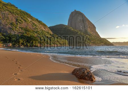The empty beach Praia Vermelha and Sugarloaf mountain on the background at sunny early morning, Rio de Janeiro, Brazil