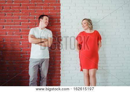 Young Attractive Couple: Pregnant Mother And Happy Father Standing Near Contrast Red And White Brick