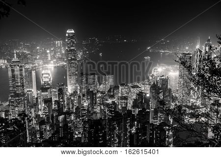 Victoria Harbour skyline by night from Lugard Road Lookout at Victoria Peak, the highest mountain in Hong Kong Island. Panorama of skyscrapers and towers of Hong Kong in black and white.