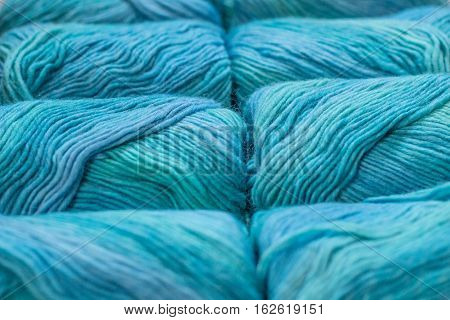 Several skeins of blue, green and turquoise yarn lying on a neutral wooden background
