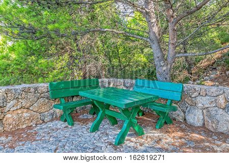 The resting place with a green wooden benches and table in Tucepi old village in the slope of a mountain Biokovo, Croatia.